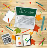 Компьтер-книжка с назад к сообщению школы, калькулятору, листьям осени и школьным принадлежностям на деревянной предпосылке - взг Стоковая Фотография