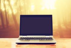 Компьтер-книжка с пустым экраном над деревянным столом outdoors и запачканной предпосылкой деревьев в лесе Стоковое Изображение RF