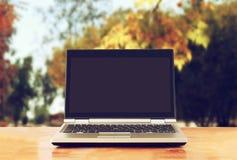 Компьтер-книжка с пустым экраном над деревянным столом outdoors и запачканной предпосылкой деревьев в лесе Стоковые Фотографии RF