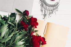 Компьтер-книжка с тетрадью, стильным ожерельем и красивыми красными пионами Стоковые Фотографии RF