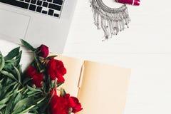 Компьтер-книжка с тетрадью, стильным ожерельем и красивыми красными пионами Стоковое Изображение RF