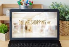 Компьтер-книжка с ходя по магазинам онлайн прибором над предпосылкой магазина нерезкости дальше Стоковая Фотография RF