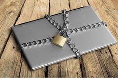 Компьтер-книжка с цепями и padlock на деревянном Стоковая Фотография