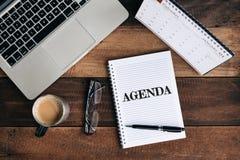 Компьтер-книжка, тетрадь, стекла, кружка кофе и календарь с словом ПОВЕСТКИ ДНЯ на деревянном столе стоковые изображения
