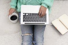 Компьтер-книжка, тетрадь и чашка кофе в руках девушки сидя дальше Стоковое фото RF