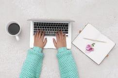 Компьтер-книжка, тетрадь и чашка кофе в руках девушки сидя дальше Стоковое Фото