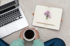 Компьтер-книжка, тетрадь и чашка кофе в руках девушки сидя дальше Стоковые Изображения RF