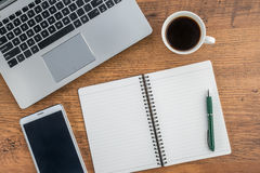 Компьтер-книжка, тетрадь, таблетка и кофе на столе работы Стоковое фото RF