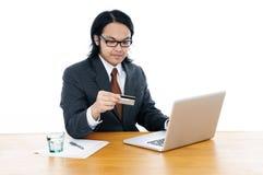 компьтер-книжка удерживания кредита карточки бизнесмена используя Стоковая Фотография