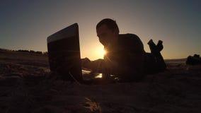 Компьтер-книжка человека компьтер-книжка человека фрилансера бизнесмена работая за сидеть на пляже работать силуэт в солнце Стоковое фото RF