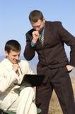 компьтер-книжка 2 бизнесменов наблюдая Стоковые Изображения RF