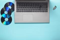 Компьтер-книжка, CD-приводы, привод вспышки USB на голубой предпосылке Современные и устаревшие цифровые средства массовой информ Стоковые Изображения