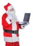компьтер-книжка santa удерживания claus thumbs вверх Стоковое Изображение