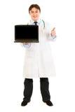 компьтер-книжки удерживания доктора показывая большие пальцы руки вверх Стоковые Изображения