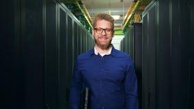 Компьутерный инженер стоит в блоке и усмехаться сервера Концепция безопасностью сети ИТ видеоматериал