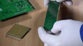 Компьютерный специалист рассматривает модуль оперативной памяти на деревянной предпосылке видеоматериал