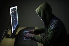 Компьютерный хакер в клобуке работая в коде темной комнаты на сетях ПК и мотыги стоковое изображение rf