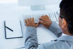 компьютер бизнесмена его используя Стоковая Фотография RF