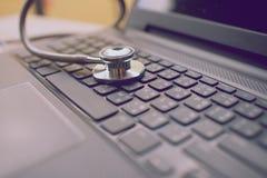 Компьютер или анализ данных - стетоскоп над клавиатурой тетради Стоковая Фотография