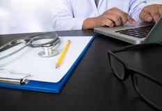 Компьютер и цифровая pro таблетка с цифровой медицинской диаграммой дальше Стоковое Изображение RF