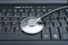 компьютер кладя стетоскоп стоковые изображения