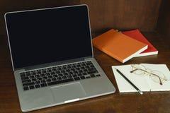 Компьютер, книги и стекла на деревянном столе Стоковые Фото