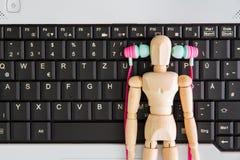 Компьютер-книжка на столе, наушник, деревянный человек стоковые изображения