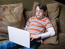 компьютер мальчика используя Стоковые Изображения