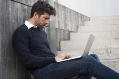 Компьютер молодого человека наблюдая Стоковые Фото