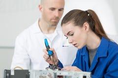 Компьютер отладки молодой женщины на столе на работе стоковое фото rf