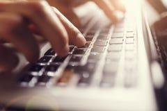 компьютер предпосылки вручает белизну компьтер-книжки печатая на машинке Стоковое Фото