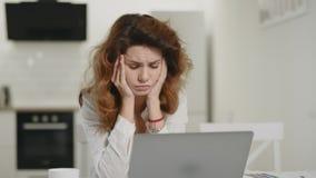 Компьютер разочарованной женщины работая дома Ноутбук вытаращиться молодой дамы на кухне сток-видео