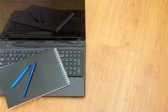 Компьютер, тетрадь и ручка предпосылки на таблице стоковое изображение