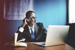 Компьютер телефона бизнесмена говоря работая Стоковые Фото
