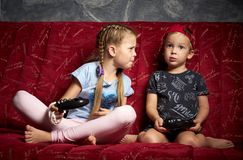 Компютерные игры: мальчик и девушка играют консоль игры в темноте и держат gamepads в их руках стоковое фото rf