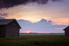 Комплекты Солнця лета между домами амбара Стоковое Изображение