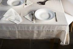 Комплекты Dinnerware и скомканной салфетки на белых покрытых Бель животиках Стоковые Изображения RF