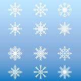 Комплект белых снежинок зимы на голубой предпосылке Стоковое Фото