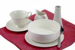 Комплект белых чашек чая помещенных на красной ткани на изолированной предпосылке Стоковое Изображение
