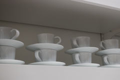 Комплект белых чашек для кофе в магазине Стоковые Фотографии RF