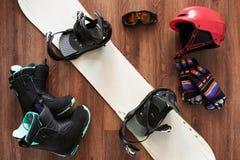 Комплект ботинок, шлема, перчаток и маски сноуборда на деревянном Стоковое фото RF