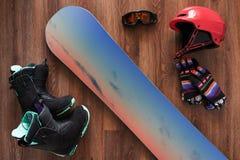 Комплект ботинок, шлема, перчаток и маски сноуборда на деревянном Стоковые Изображения RF