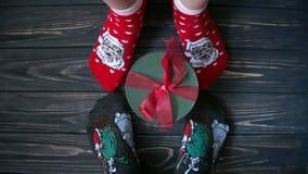 Комплект верхней части подарков на темной серой деревянной предпосылке Настоящие моменты и ноги ` s пар в носках Стоковые Фото