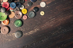 Комплект винтажных кнопок на старом деревянном столе Стоковые Изображения RF