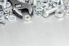 Комплект винтов и болтов с регулируемым ключем на поцарапанной мете Стоковые Фото