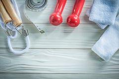 Комплект гантелей веревочки скачки измеряя sweatbands ленты на деревянном b Стоковые Фотографии RF
