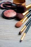 Комплект декоративных косметик и щеток на серой деревянной предпосылке Различные продукты состава коричневых цветов Взгляд сверху Стоковые Изображения RF