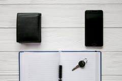 Комплект дела примечания, сотового телефона и ключа на белой деревянной предпосылке Стоковые Фото