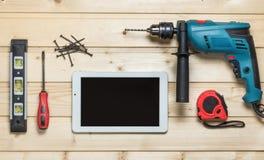 Комплект инструментов конструкции, который нужно отремонтировать на деревянном столе: белая таблетка, сверло, молоток, плоскогубц Стоковые Фотографии RF