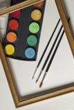 Комплект картины акварели, деревянная рамка и щетки на белой предпосылке альбома Стоковая Фотография RF